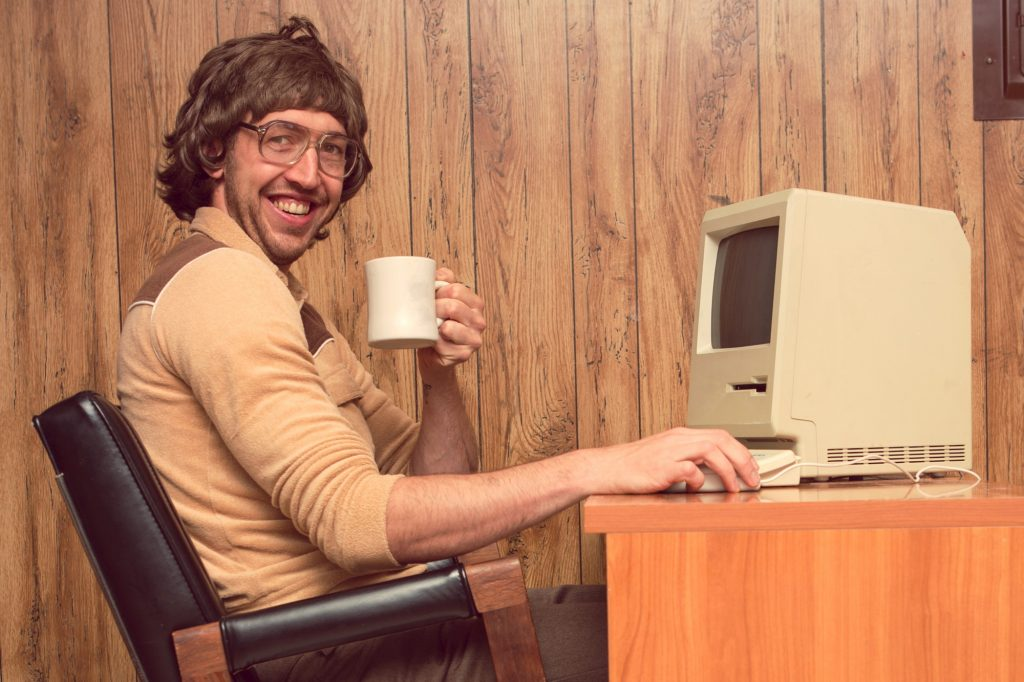An man dressed like from the 1980s, in front of a very old personal computer.